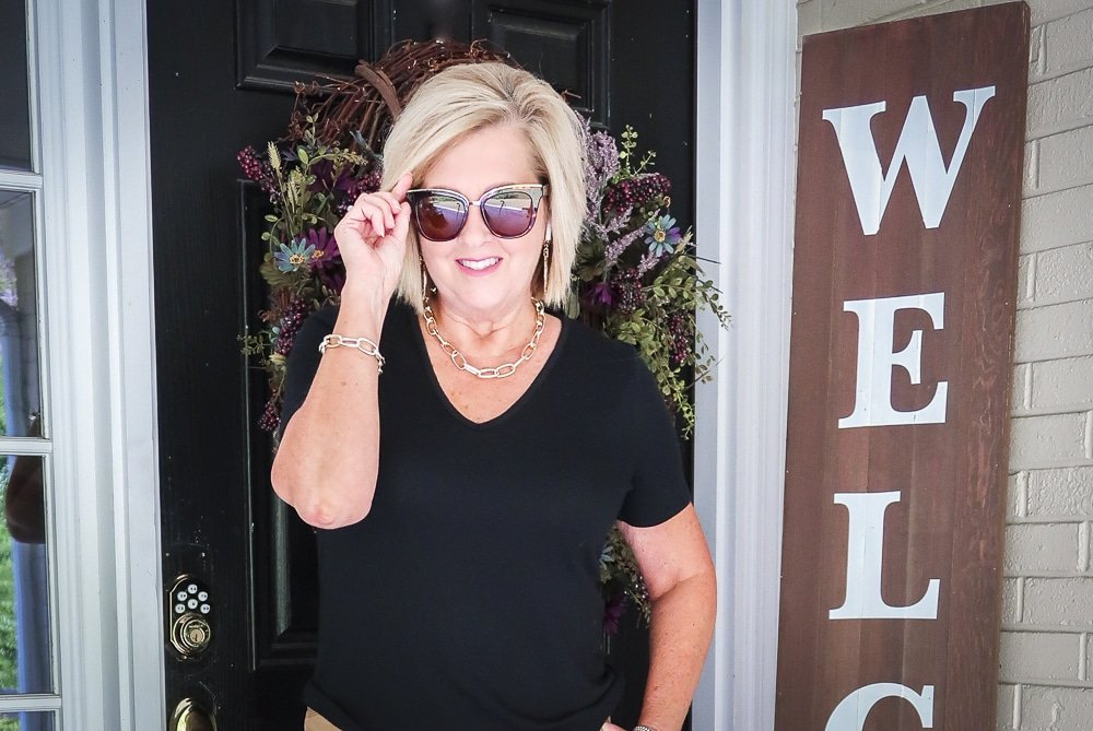 Fashion Blogger 50 Is Not Old is wearing a black t-shirt with a pair of sunglasses and gold jewerly