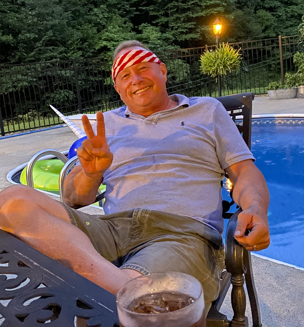 Joe Cool sitting by the pool with a striped bandana around his head