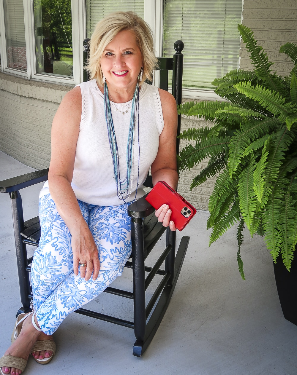 Fashion Blogger 50 Is Not Old is wearing a classic blue and white outfit sitting in a rocking chair. A white sweater, blue and white printed ankle pants from Lilly Pulitzer and espadrille wedges
