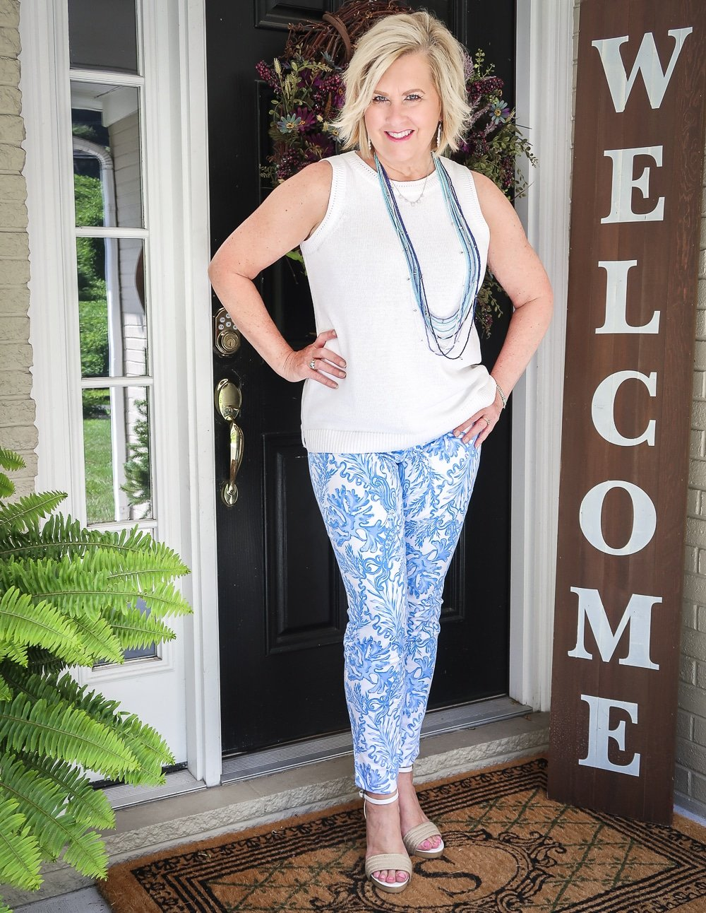 Fashion Blogger 50 Is Not Old is wearing a classic blue and white outfit. A white sweater, blue and white printed ankle pants from Lilly Pulitzer