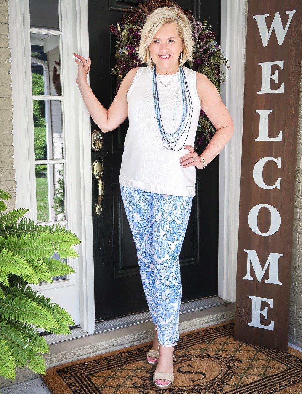 Fashion Blogger 50 Is Not Old is wearing a classic blue and white outfit. A white sweater, blue and white printed ankle pants from Lilly Pulitzer and espadrille wedges
