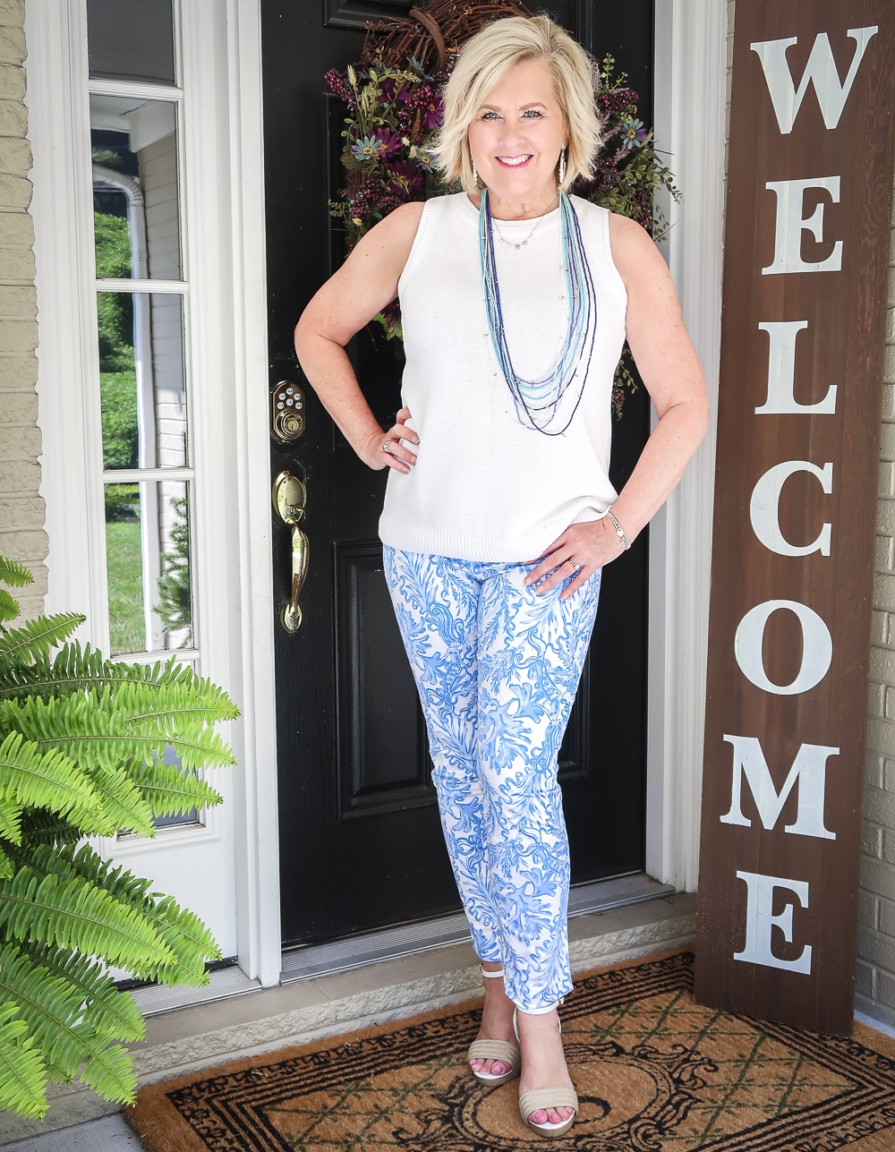 Fashion Blogger 50 Is Not Old is wearing a classic blue and white outfit. A white sweater, blue and white ankle pants from Lilly Pulitzer and espadrille wedges