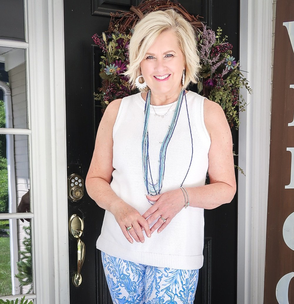 Fashion Blogger 50 Is Not Old is wearing a classic blue and white outfit. A white sweater with a blue multi strand necklace