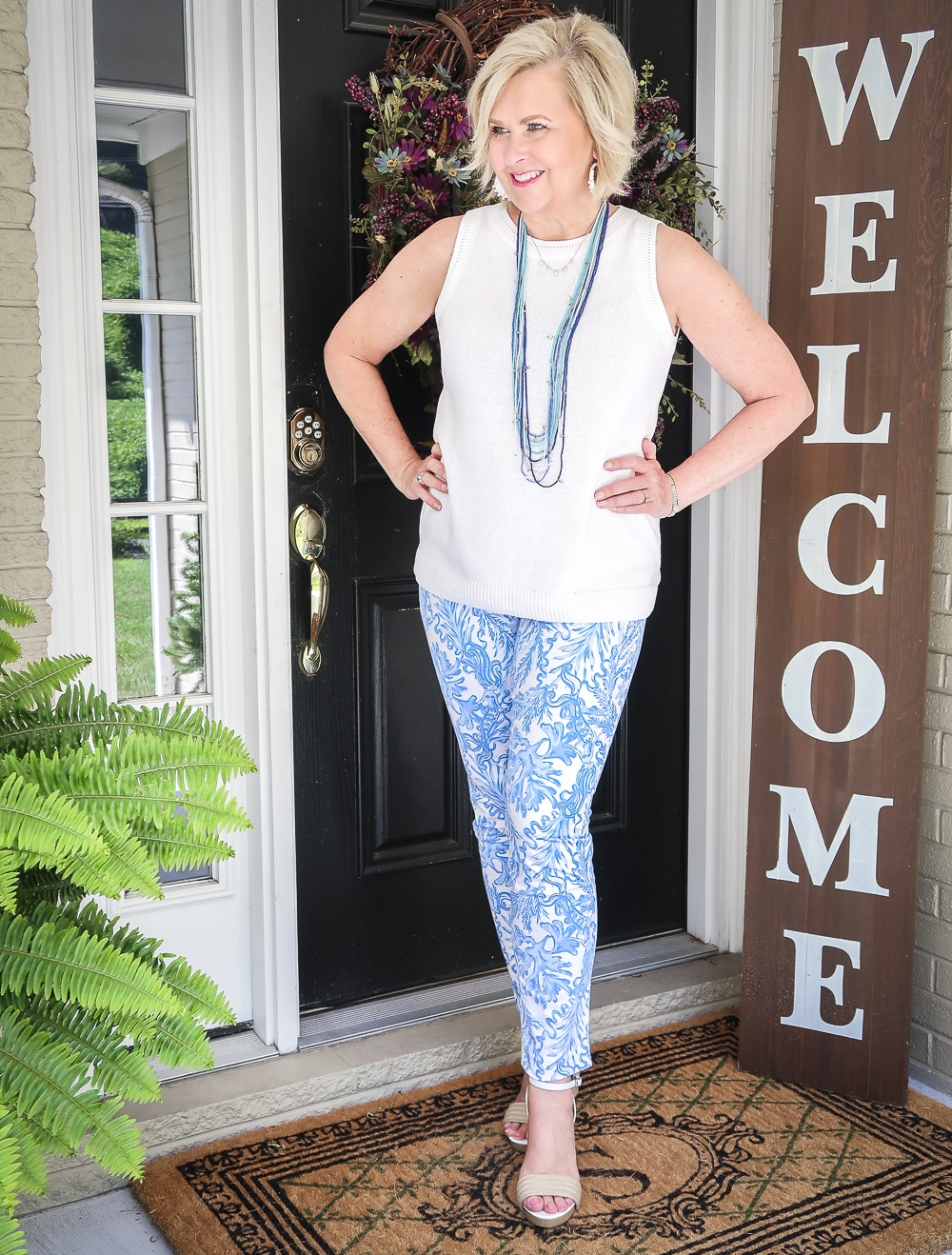 Fashion Blogger 50 Is Not Old is wearing a classic blue and white outfit. A white sweater, blue and white printed ankle pants, and espadrille wedges