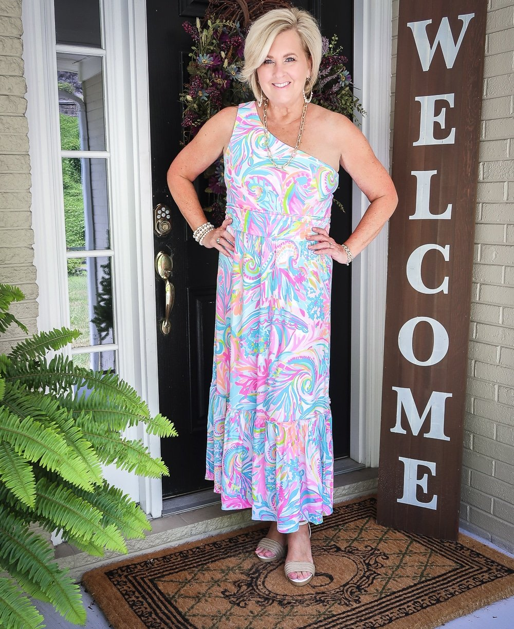 Fashion Blogger 50 Is Not Old is styling a one shoulder Lilly Pulitzer dress with gold jewelry from Kendra Scott