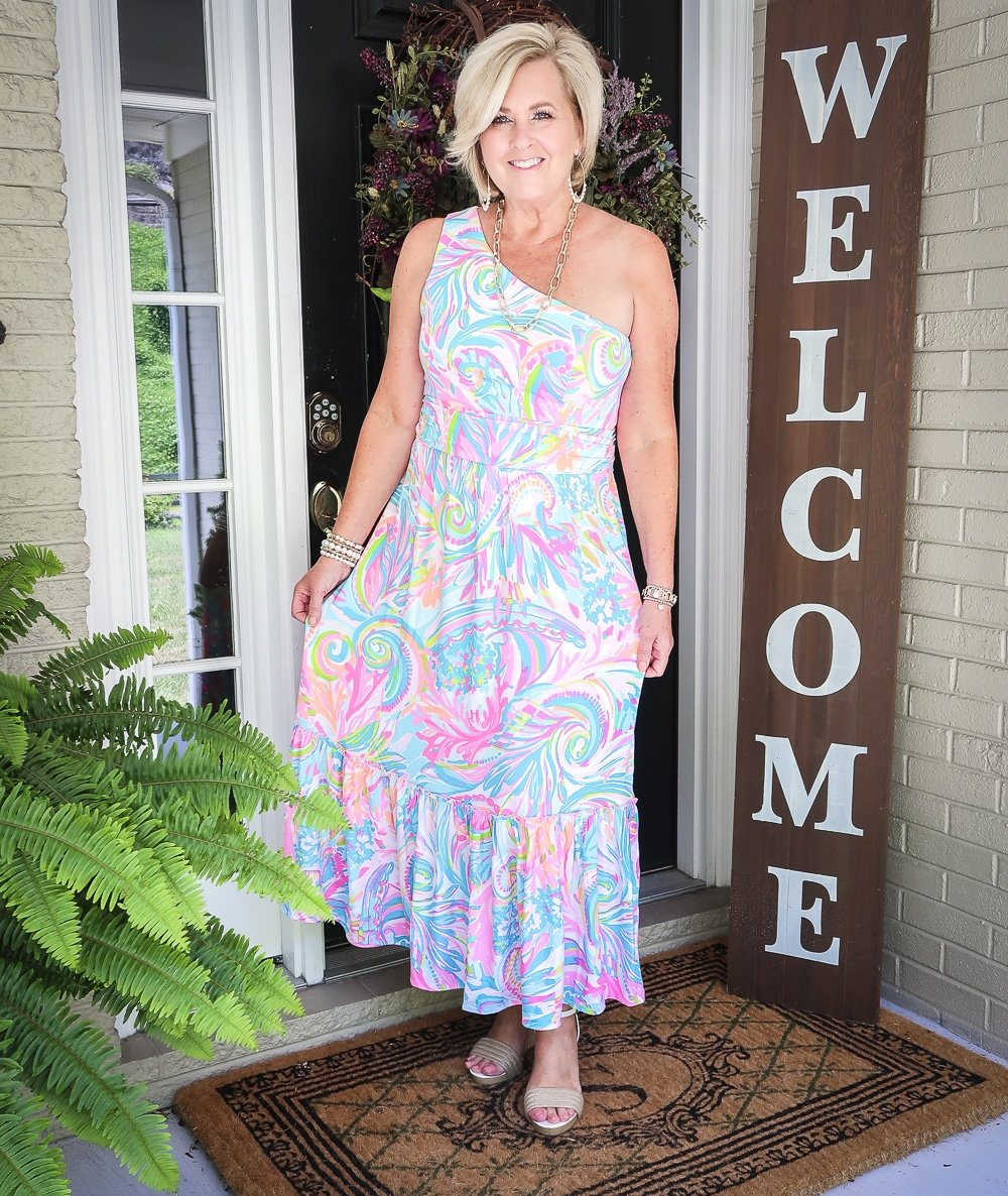 Fashion Blogger 50 Is Not Old is styling a one-shoulder Lilly Pulitzer maxi dress with gold jewelry from Kendra Scott