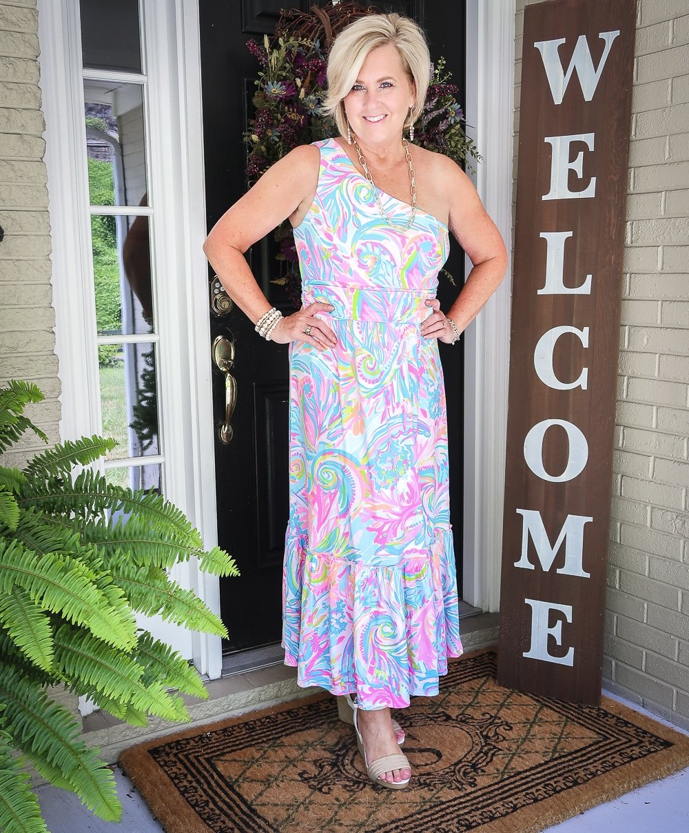 Fashion Blogger 50 Is Not Old is styling a one shoulder Lilly Pulitzer maxi dress with gold jewelry from Kendra Scott