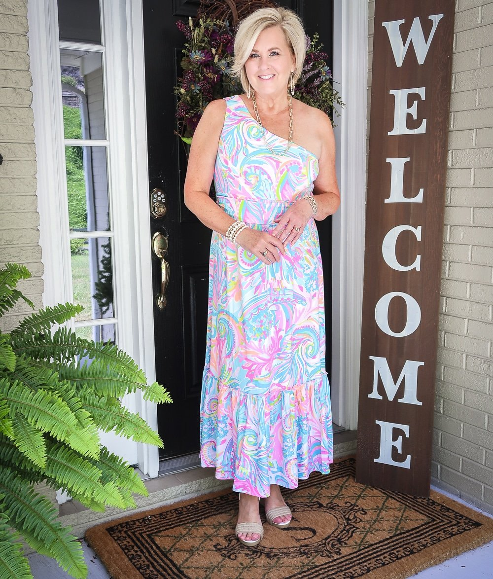 Fashion Blogger 50 Is Not Old is styling a one shoulder Lilly Pulitzer maxi dress, gold jewelry from Kendra Scott, and espadrille shoes