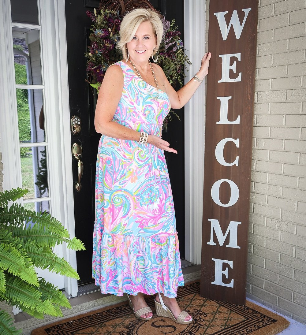 Fashion Blogger 50 Is Not Old is welcoming you and styling a one shoulder Lilly Pulitzer maxi dress with gold jewelry from Kendra Scott