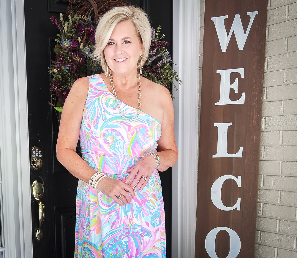 Fashion Blogger 50 Is Not Old is styling a one shoulder Lilly Pulitzer maxi dress with gold jewelry