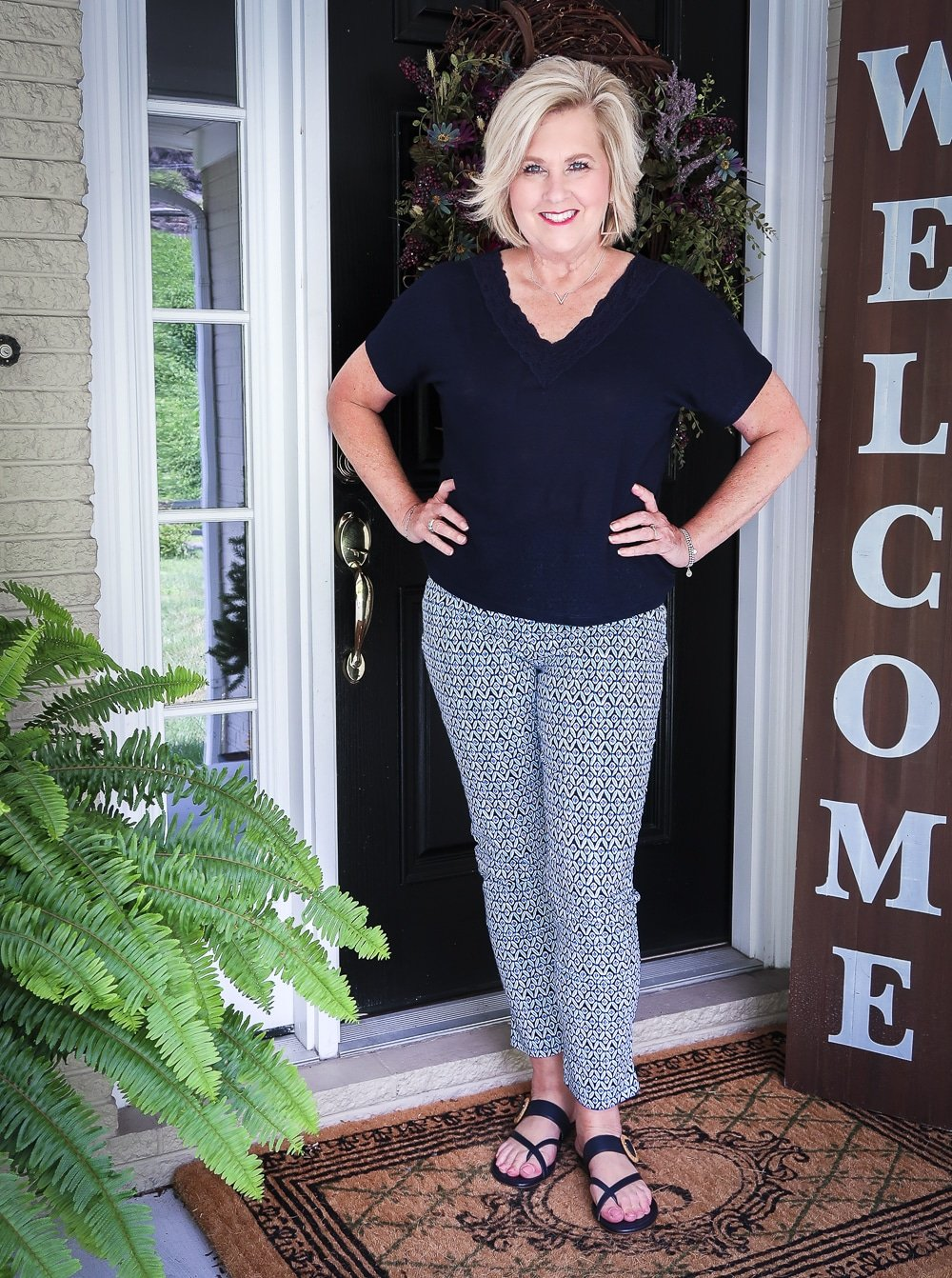 Fashion Blogger 50 Is Not Old wearing a dark navy linen top with a lace neckline and blue printed ankle pants with navy sandals