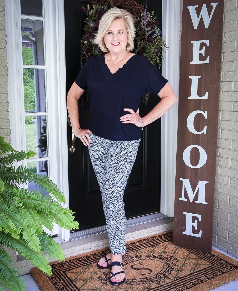 Fashion Blogger 50 Is Not Old wearing a dark navy linen top with a lace neckline and printed ankle pants with navy sandals from Talbots