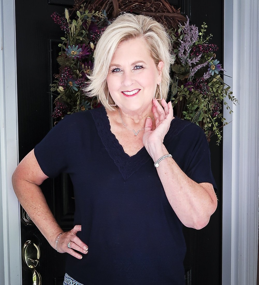 Fashion Blogger 50 Is Not Old wearing a dark navy linen top with a lace neckline and silver jewelry