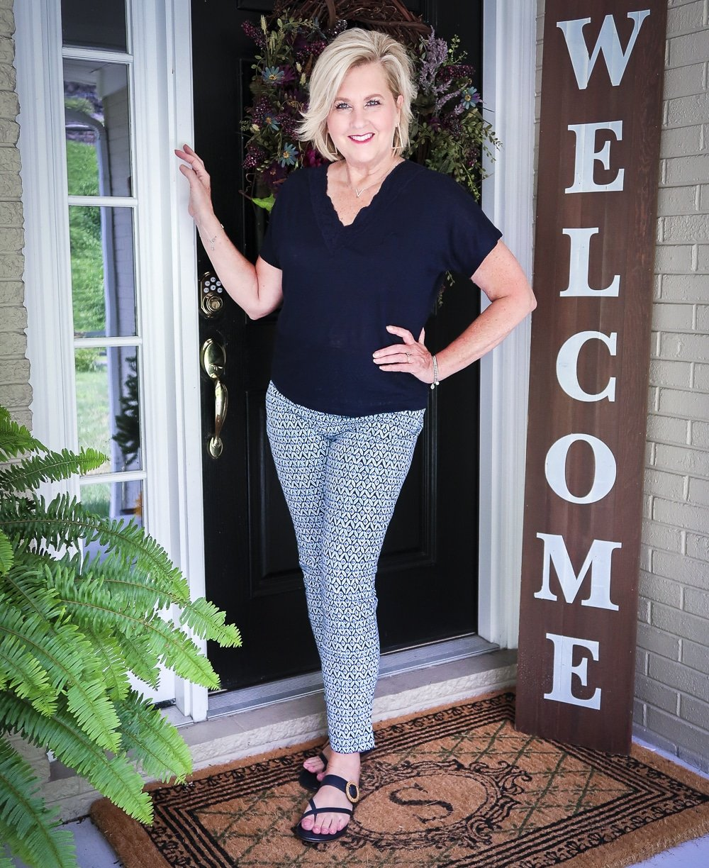 Fashion Blogger 50 Is Not Old wearing a dark navy linen top with a lace neckline and printed ankle pants with navy sandals