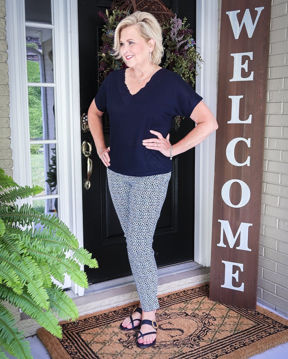 Fashion Blogger 50 Is Not Old is looking away and wearing a dark navy linen top with a lace neckline and printed ankle pants with navy sandals
