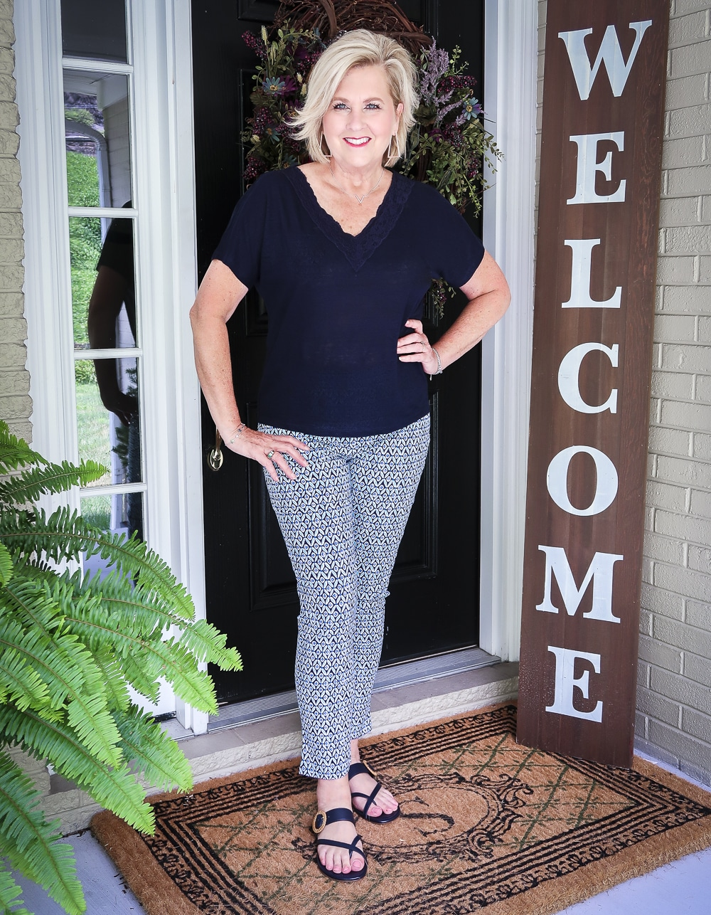 Fashion Blogger 50 Is Not Old wearing a navy linen top with a lace neckline and printed ankle pants with navy sandals