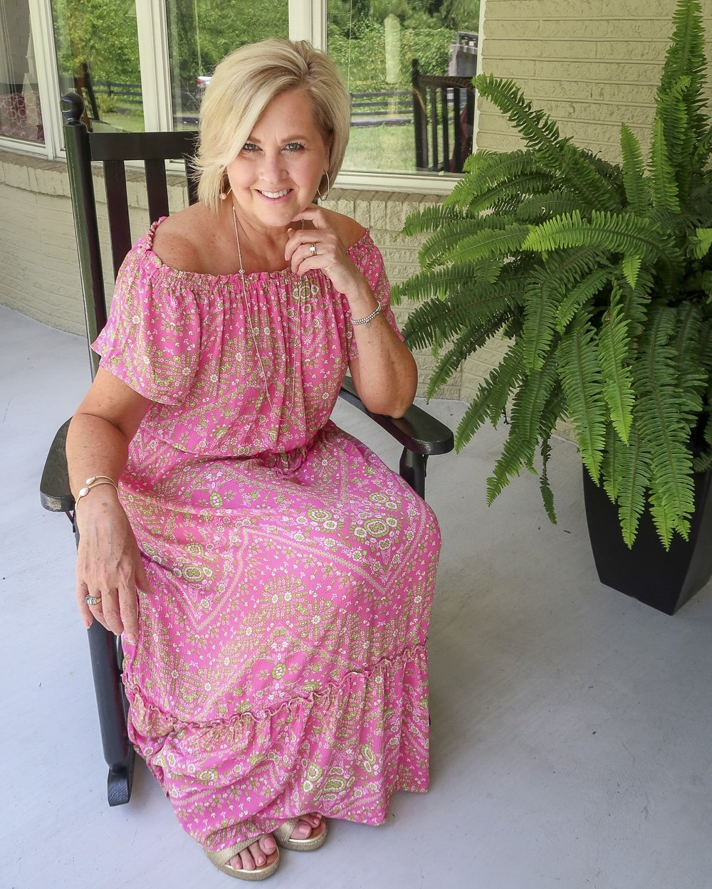 Fashion Blogger 50 Is Not Old is in a rocking chair and wearing an off the shoulder pink dress with delicate gold jewelry and gold wedge espadrilles