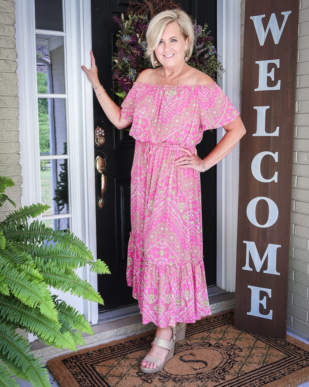 Fashion Blogger 50 Is Not Old is wearing an off the shoulder pink dress with delicate gold jewelry and gold wedge espadrilles