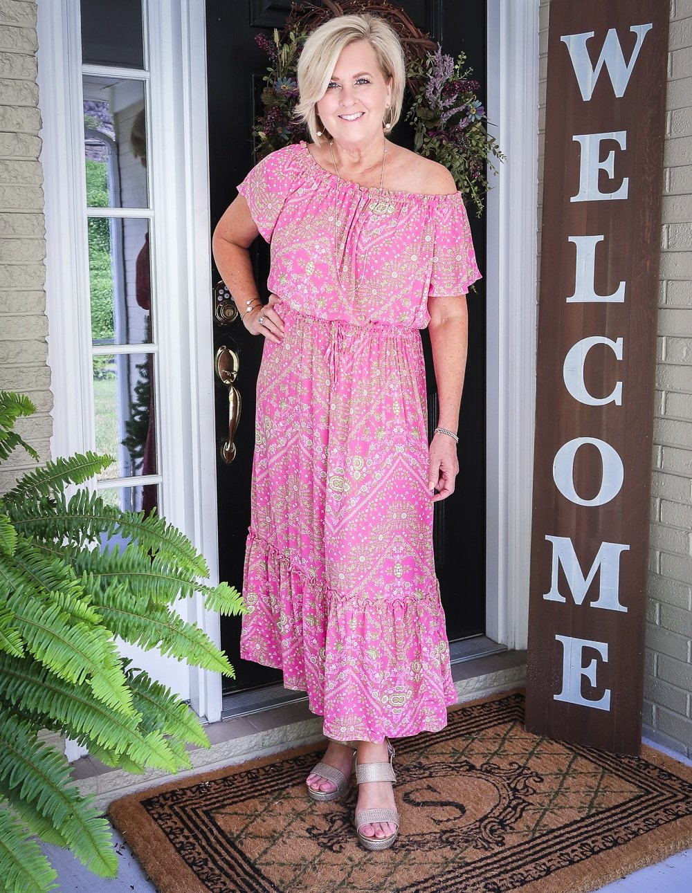Fashion Blogger 50 Is Not Old is wearing an off the shoulder pink dress with gold jewelry and gold wedge espadrilles
