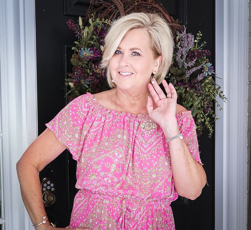 Fashion Blogger 50 Is Not Old is wearing an off the shoulder pink dress with delicate gold jewelry