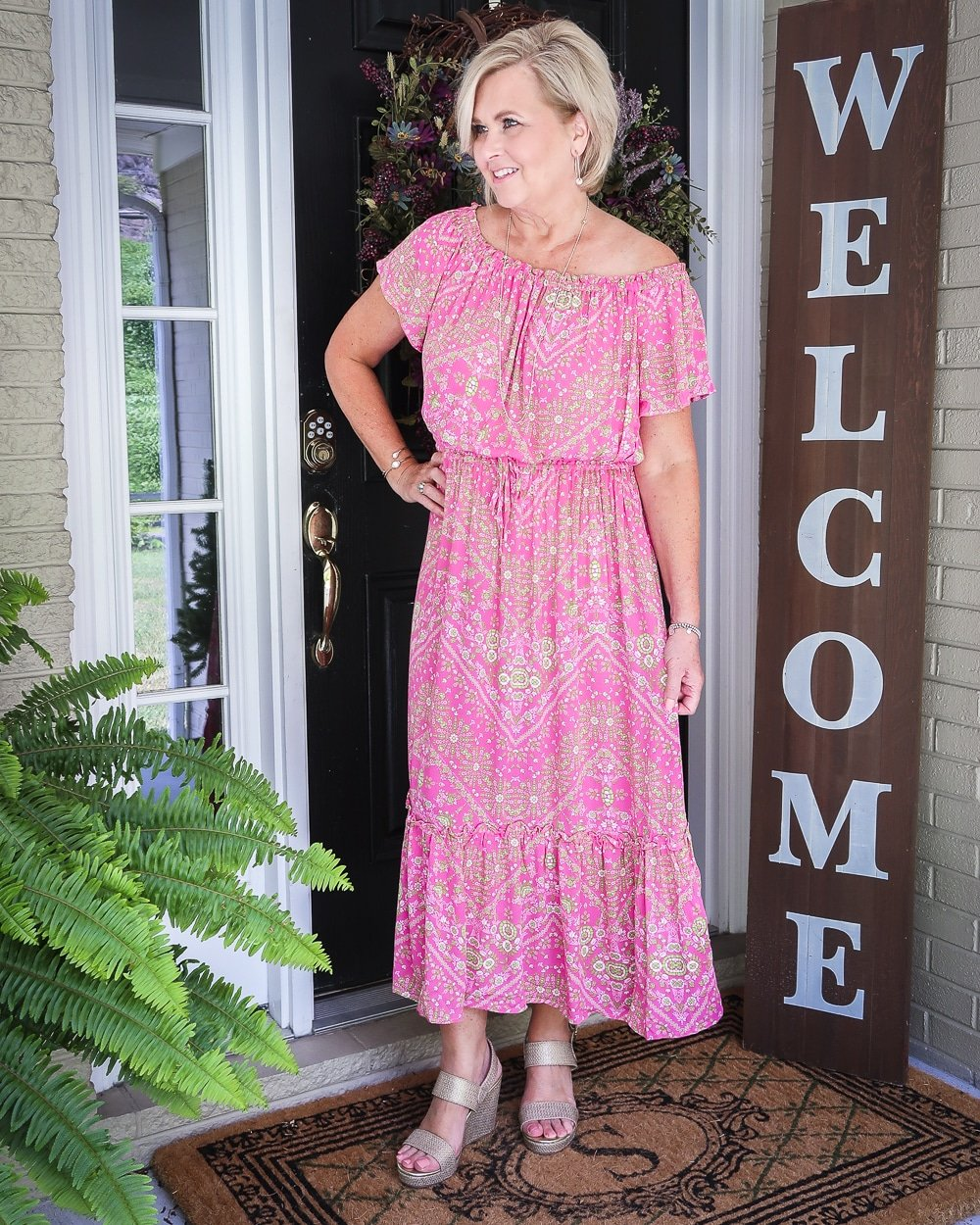 Fashion Blogger 50 Is Not Old is looking to the side and wearing an off the shoulder pink dress with delicate gold jewelry and gold wedge espadrilles
