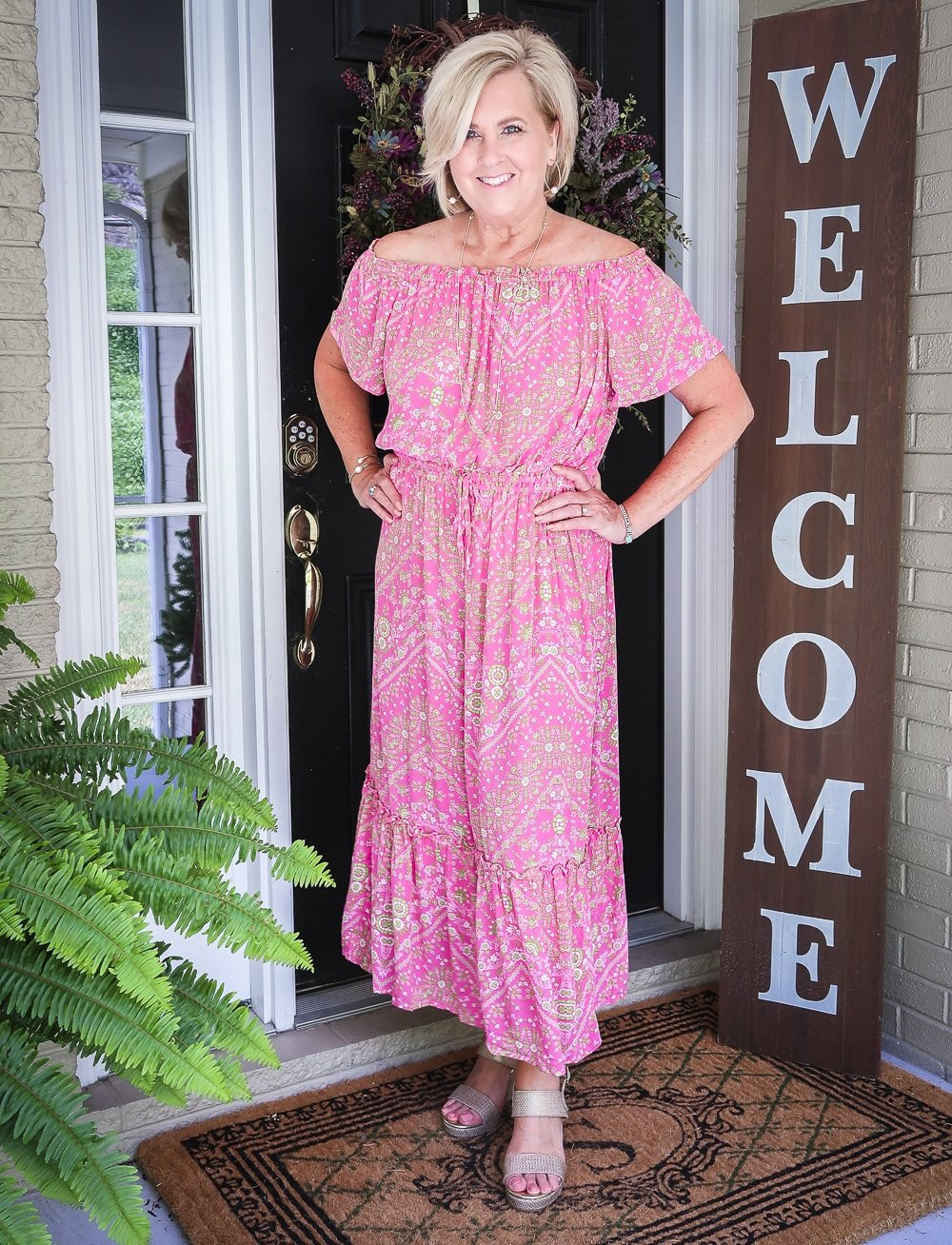 Fashion Blogger 50 Is Not Old is wearing an off the shoulder pink dress with gold jewelry and wedge espadrilles