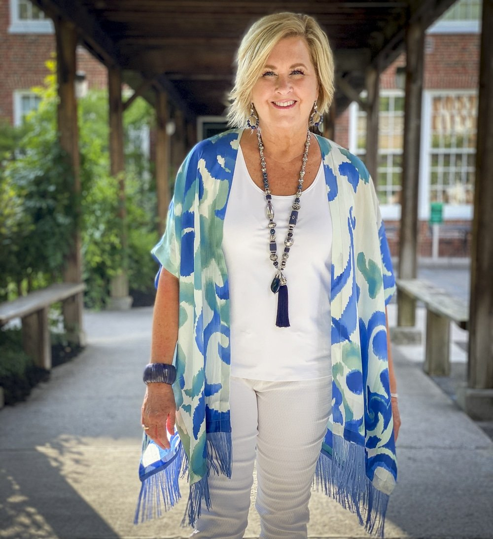 Fashion Blogger 50 Is Not Old is wearing a white tank top, white textured crop pants, and a colorful silk ruana from Chicos with a long navy necklace