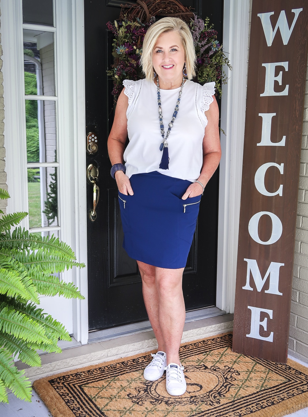 Fashion Blogger 50 Is Not Old is wearing an eyelet flutter sleeve top with a navy skort with zippers and a pair of Sperry no-tie sneakers