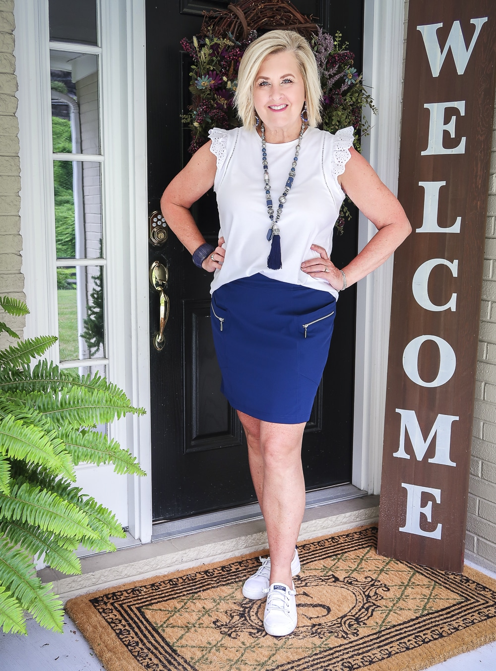 Fashion Blogger 50 Is Not Old is wearing an eyelet flutter sleeve top with a navy skort with zippers and a pair of white Sperry no-tie sneakers
