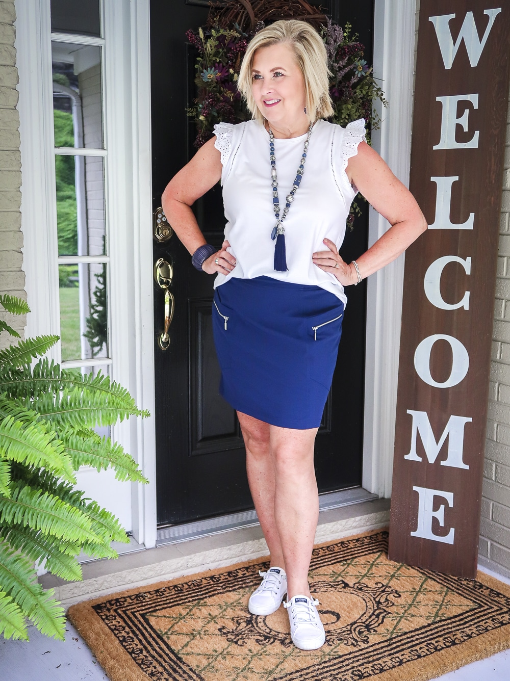 Fashion Blogger 50 Is Not Old is wearing an eyelet flutter sleeve top with a navy skort with zippers and a pair of white no-tie sneakers
