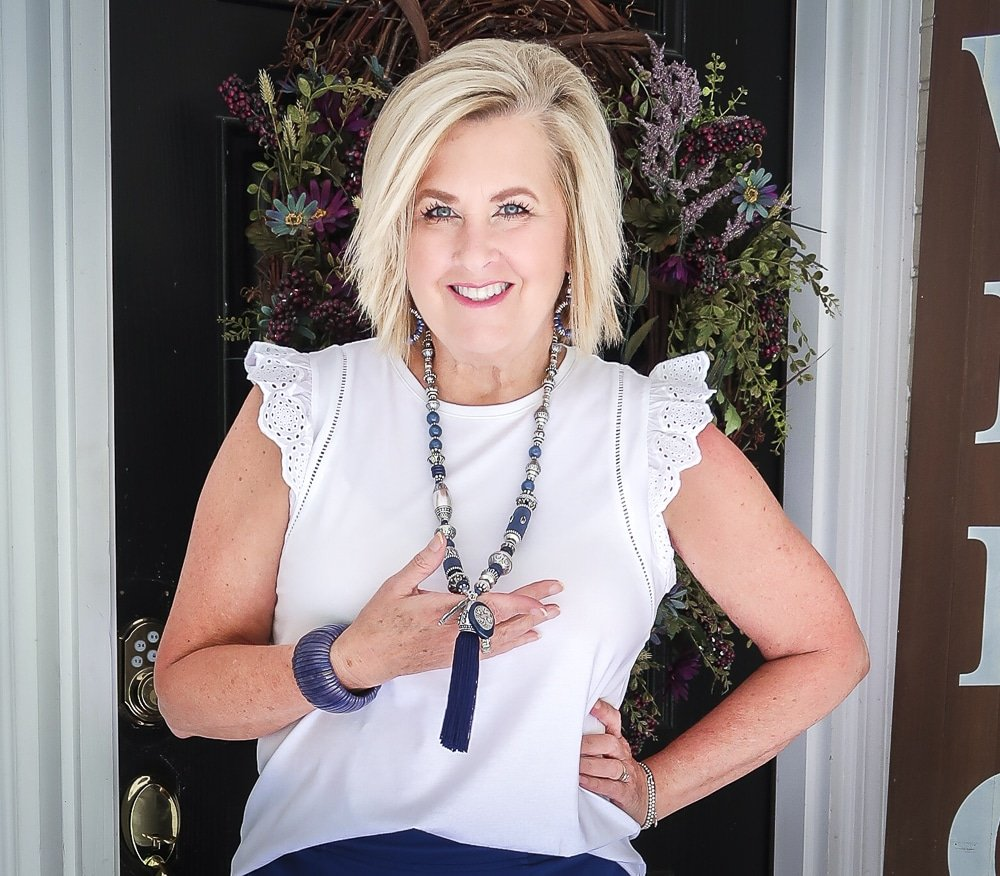 Fashion Blogger 50 Is Not Old is wearing an eyelet flutter sleeve top with navy and silver jewelry