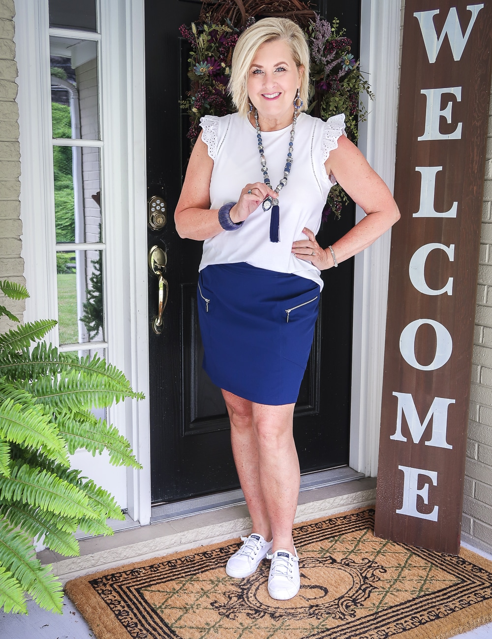 Fashion Blogger 50 Is Not Old is wearing an eyelet flutter sleeve top with a navy skort with silver zippers and a pair of Sperry no-tie sneakers