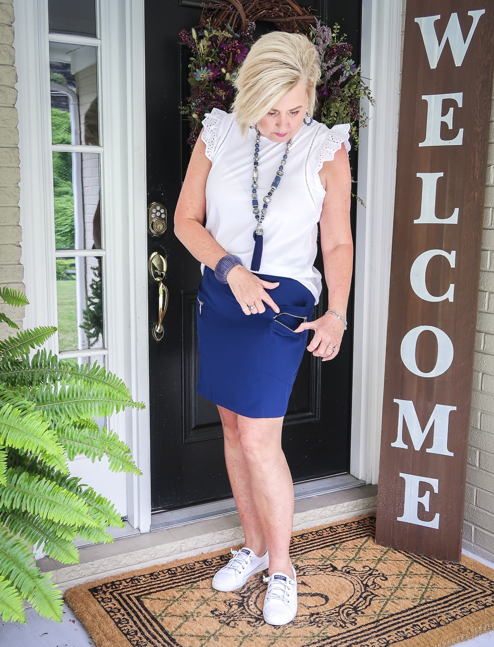Fashion Blogger 50 Is Not Old is wearing a white eyelet flutter sleeve top with a navy skort with zippers
