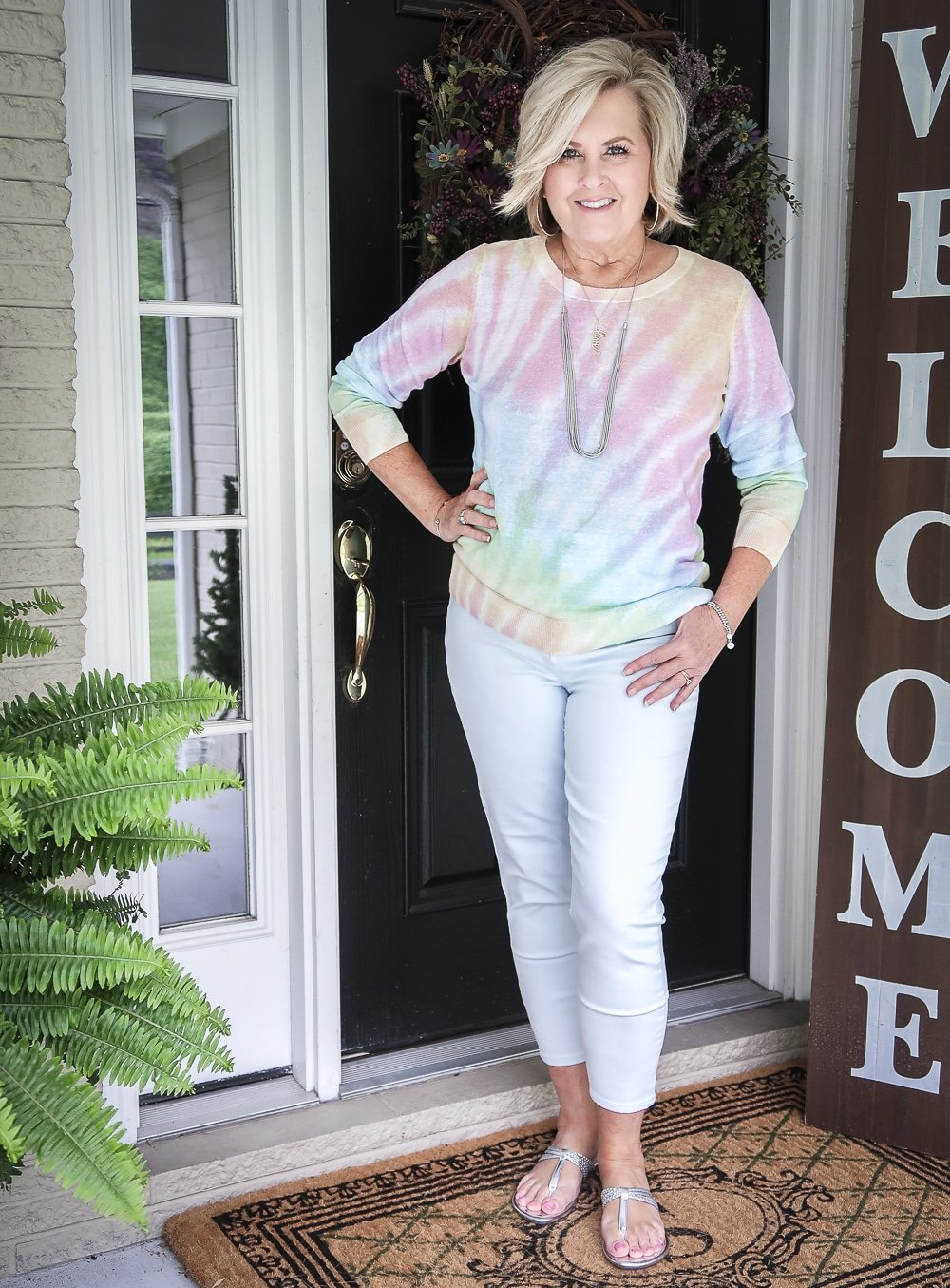 Fashion Blogger 50 Is Not Old is wearing a gorgeous tie-dye sweater with pale blue jeggings and silver braided sandals