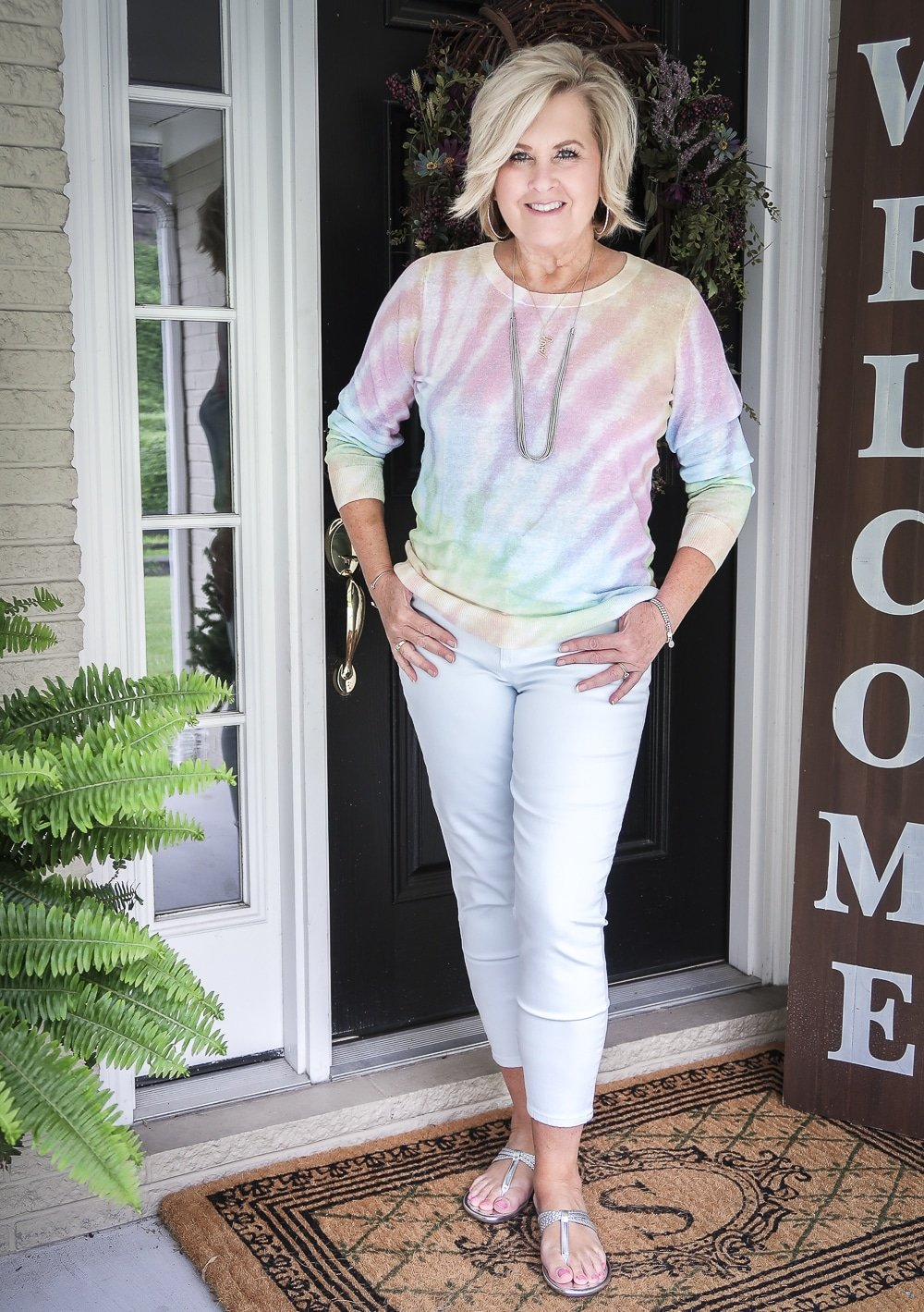 Fashion Blogger 50 Is Not Old is wearing a gorgeous tie-dye sweater with pale blue jeggings and braided sandals