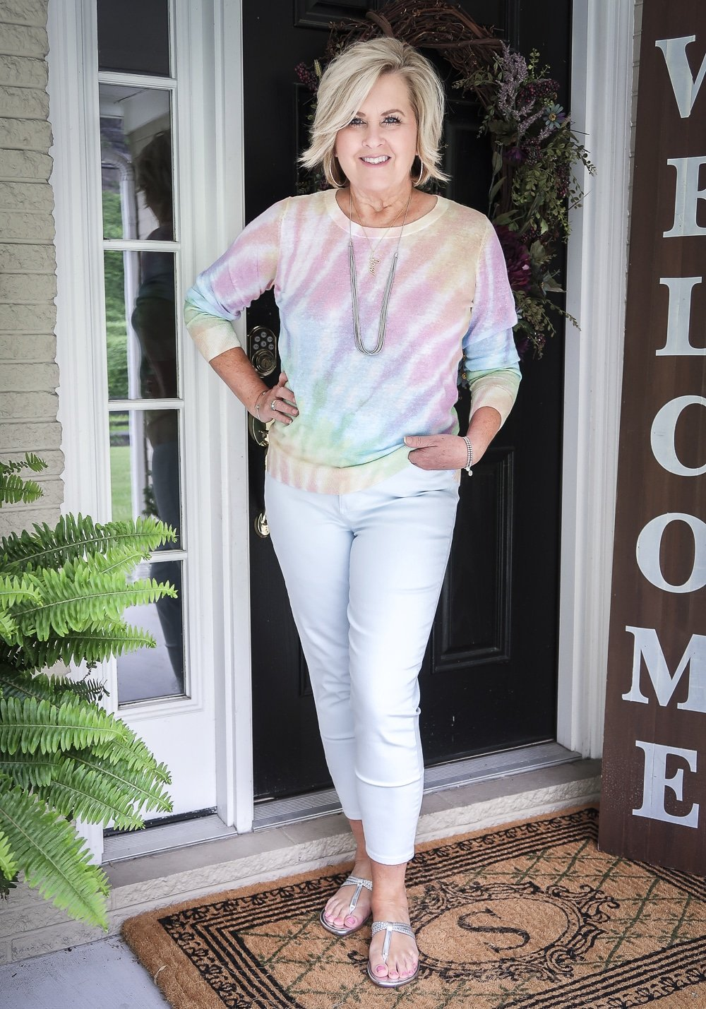 Fashion Blogger 50 Is Not Old is wearing a gorgeous tie-dye sweater with pale blue jeggings and silver sandals