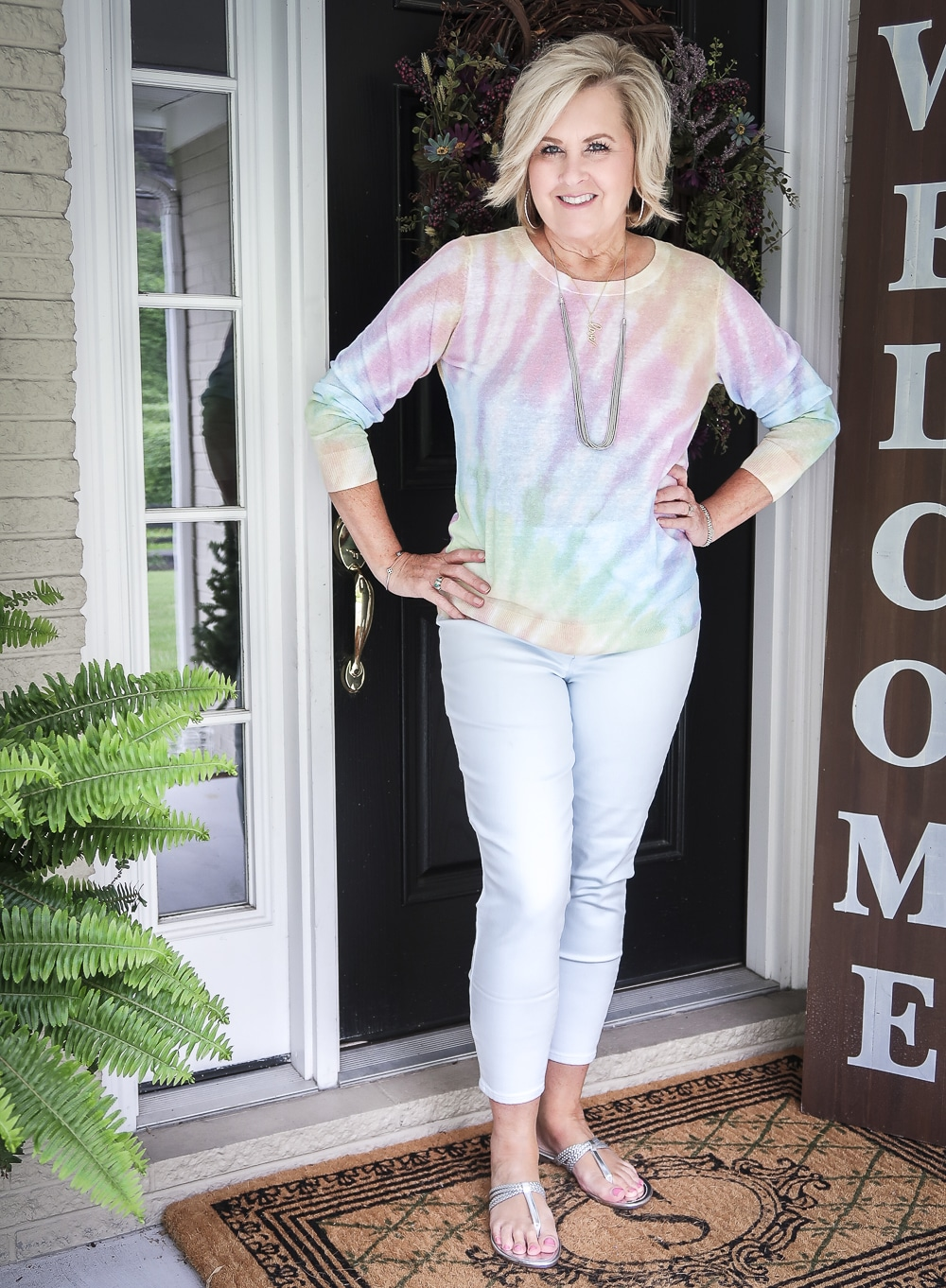 Fashion Blogger 50 Is Not Old is wearing a gorgeous tie-dye sweater with pale blue pants and silver braided sandals