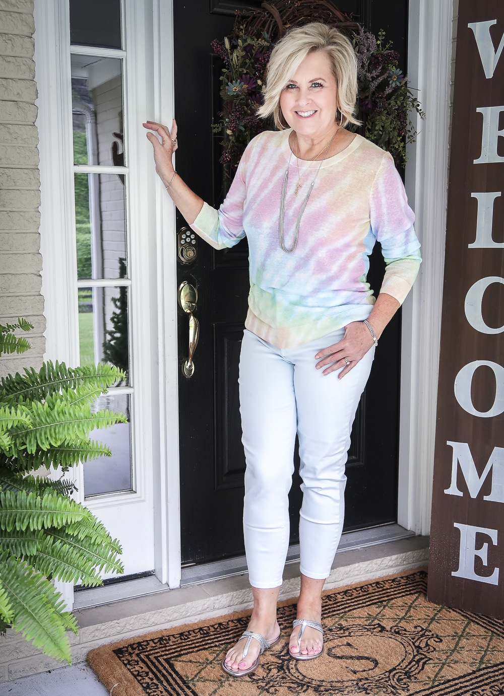 Fashion Blogger 50 Is Not Old is wearing a tie-dye sweater with pale blue jeggings and silver braided sandals
