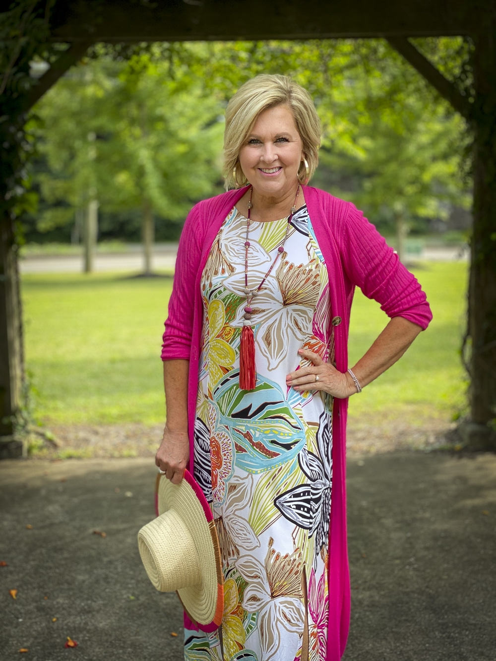 Fashion Blogger 50 Is Not Old is wearing a pink cardigan with a tropical print sleeveless dress with colorful accessories