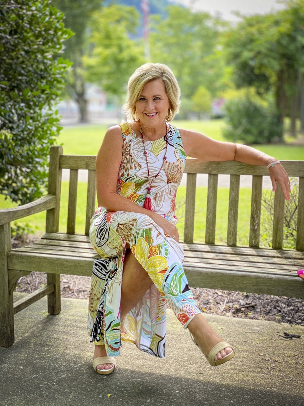 Fashion Blogger 50 Is Not Old is sitting down while wearing a tropical print sleeveless dress with colorful accessories and white espadrilles