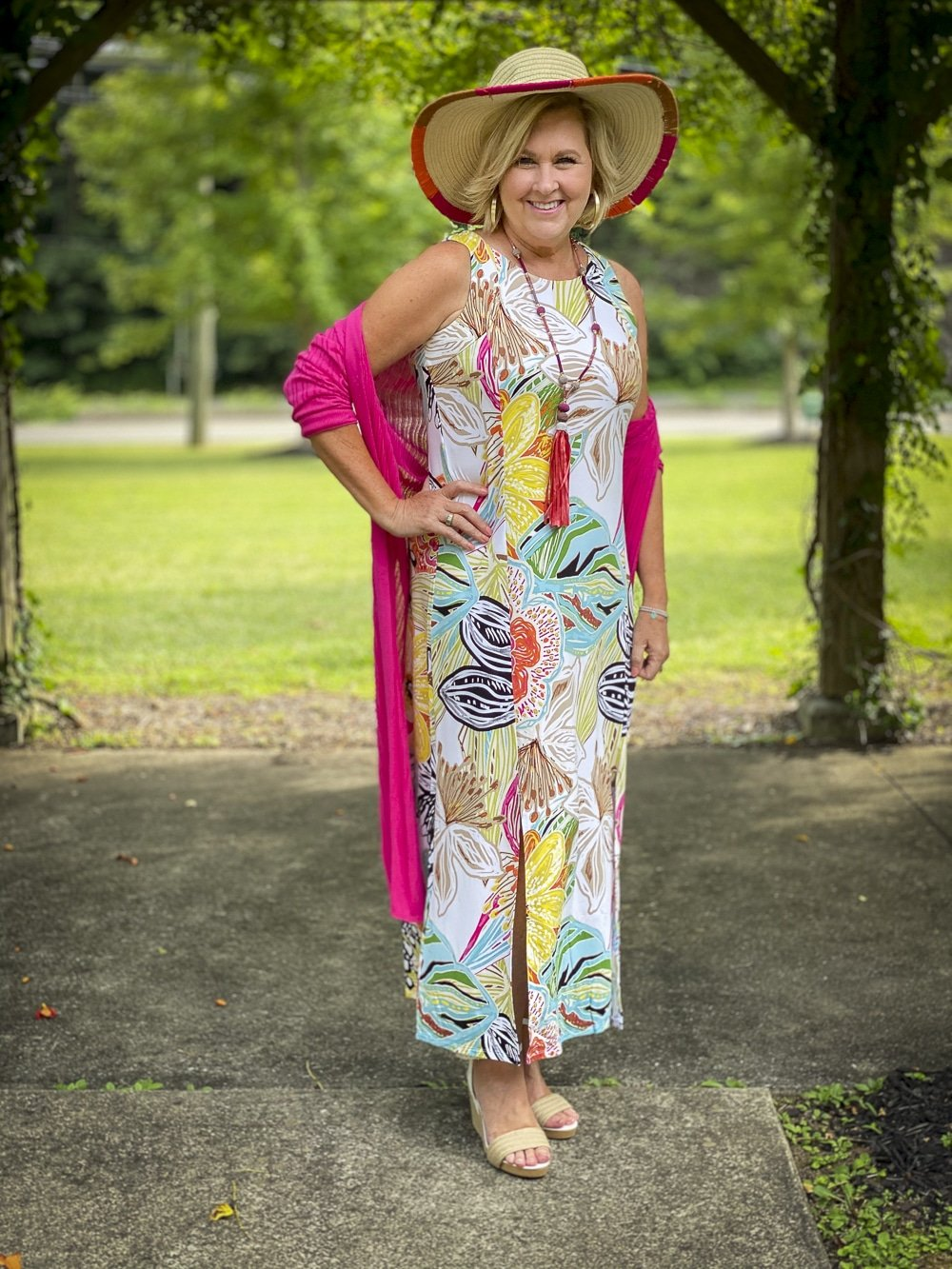 Fashion Blogger 50 Is Not Old is wearing a tropical print sleeveless dress, a pink cardigan, colorful accessories and white espadrilles