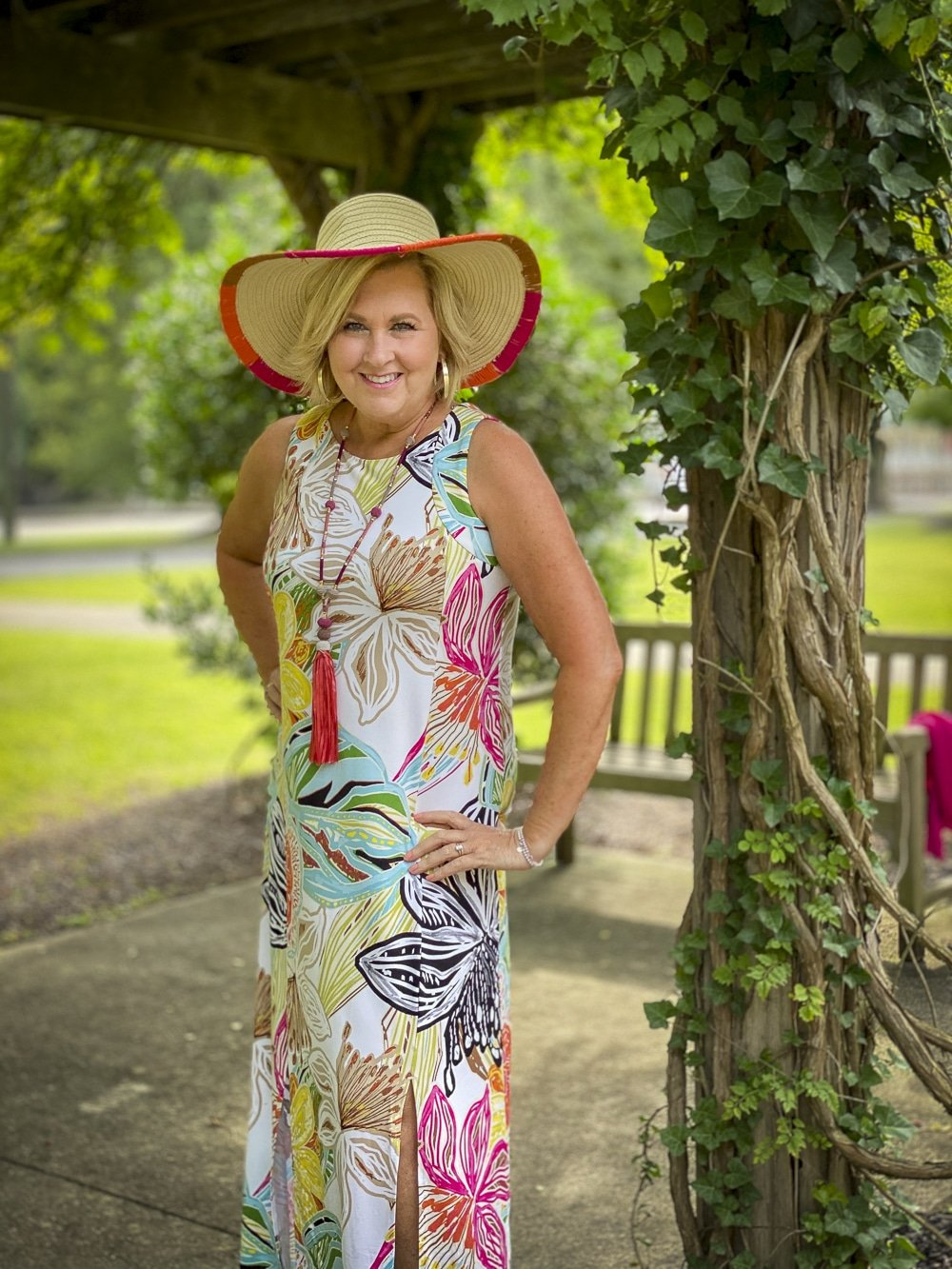 Fashion Blogger 50 Is Not Old is wearing a tropical print sleeveless dress with colorful accessories