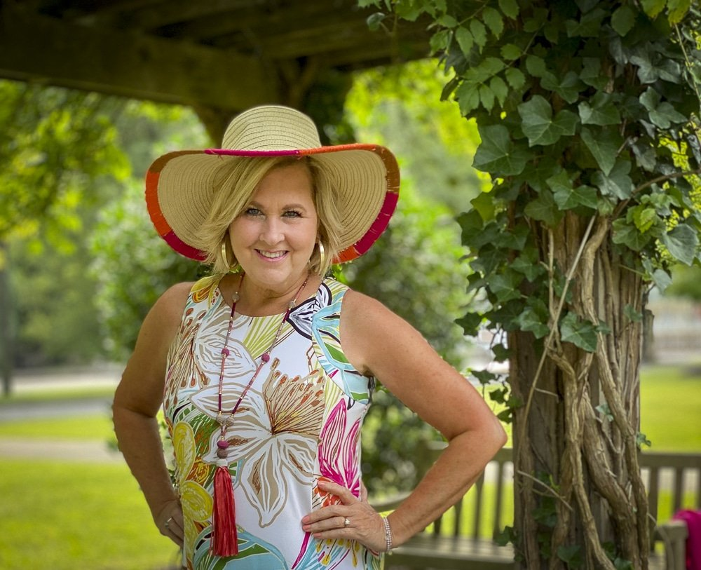 Fashion Blogger 50 Is Not Old is wearing a tropical print sleeveless dress with a straw hat