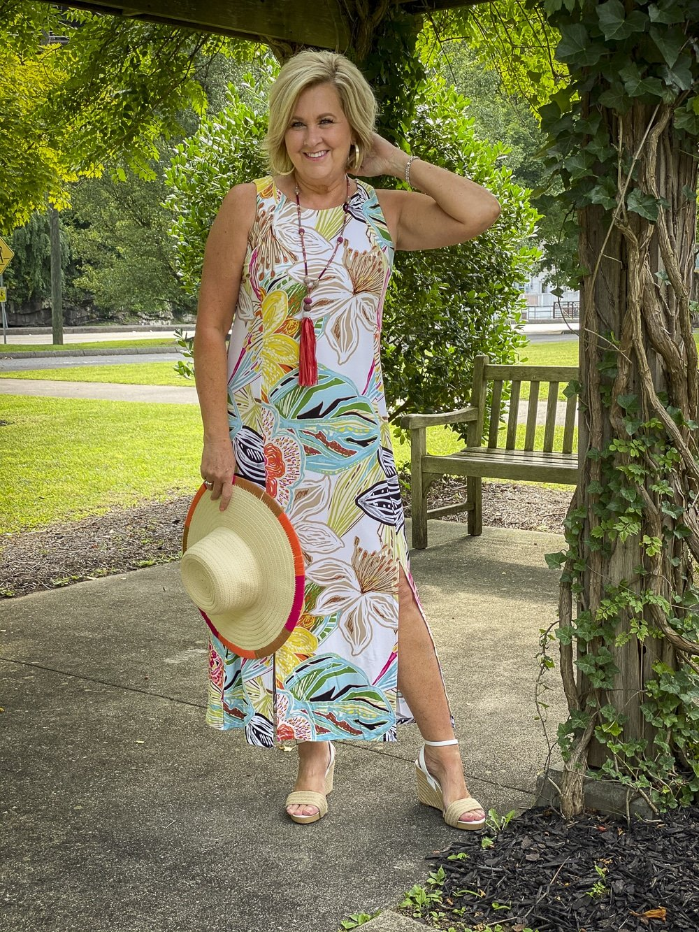 Fashion Blogger 50 Is Not Old is wearing a tropical print sleeveless dress with colorful accessories and white espadrilles