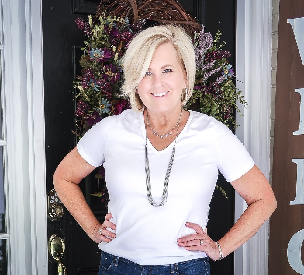 Fashion Blogger 50 Is Not Old is wearing a white v neck t-shirt, distressed jean shorts