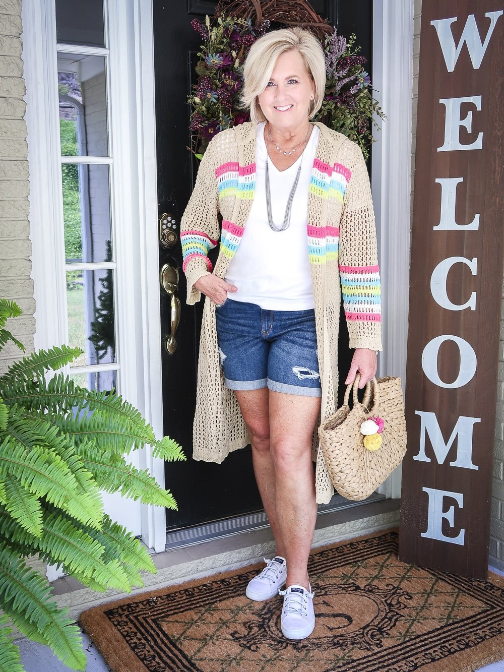 Fashion Blogger 50 Is Not Old is wearing a white v neck t-shirt, distressed jean shorts, and a open knit long cardigan with no-tie sneakers