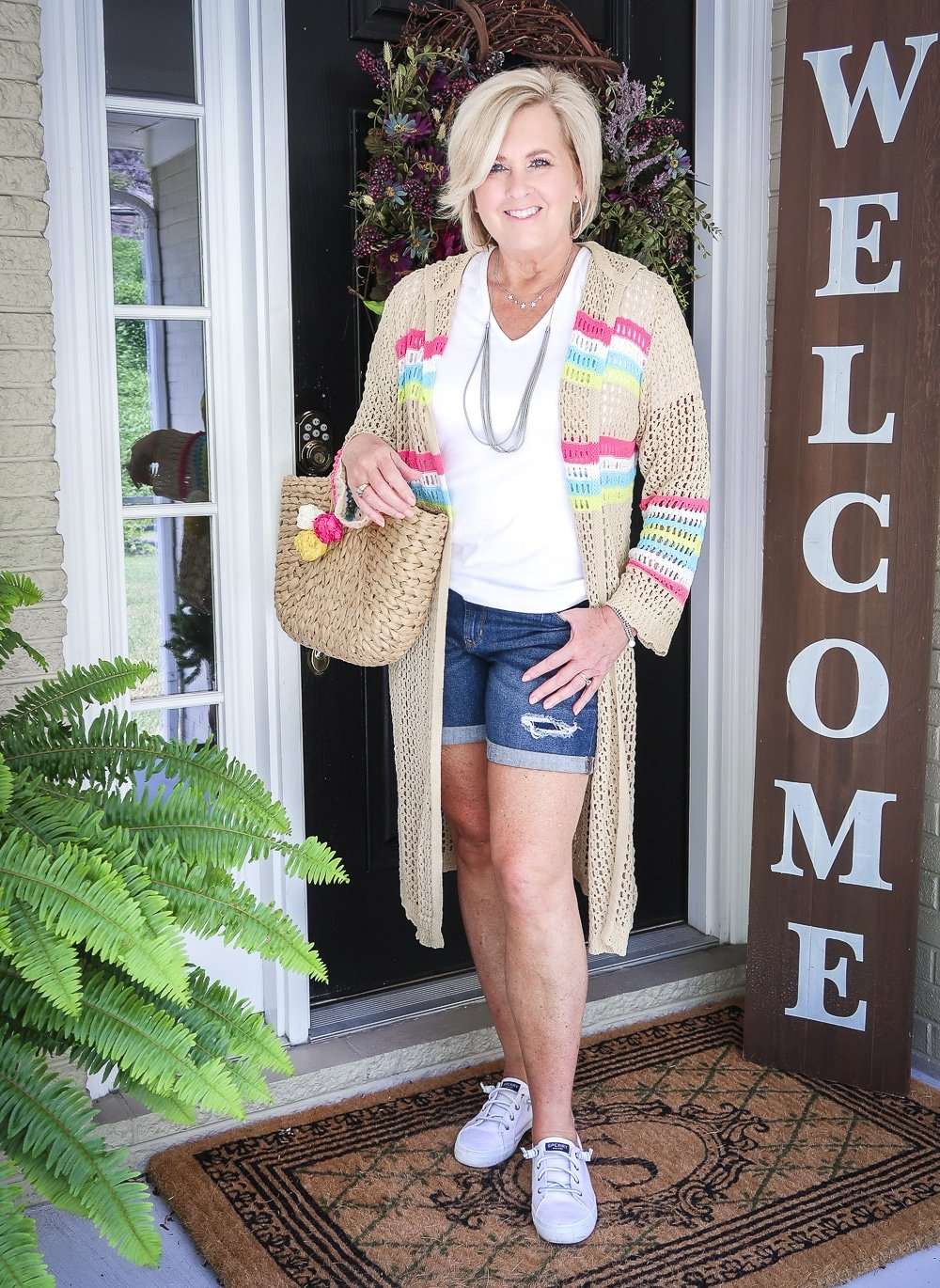 Fashion Blogger 50 Is Not Old is wearing a white v neck t-shirt, distressed jean shorts, carrying a straw bag, and a open knit long cardigan with Sperry no-tie sneakers