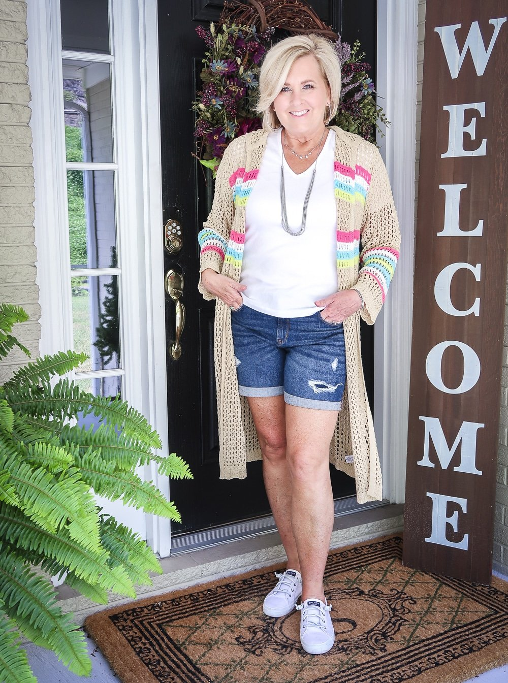 Fashion Blogger 50 Is Not Old is wearing a white v neck t-shirt, distressed jean shorts, and a open knit long cardigan with Sperry no-tie sneakers