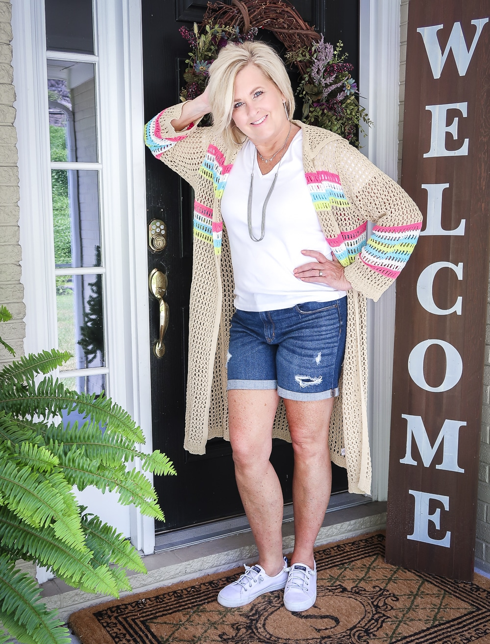 Fashion Blogger 50 Is Not Old is leaning on a door wearing a white v neck t-shirt, distressed jean shorts, and a open knit long cardigan with Sperry no-tie sneakers