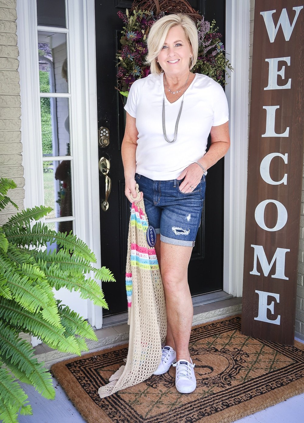 Fashion Blogger 50 Is Not Old is wearing a white v neck t-shirt, distressed jean shorts, holding an open knit long cardigan with Sperry no-tie sneakers